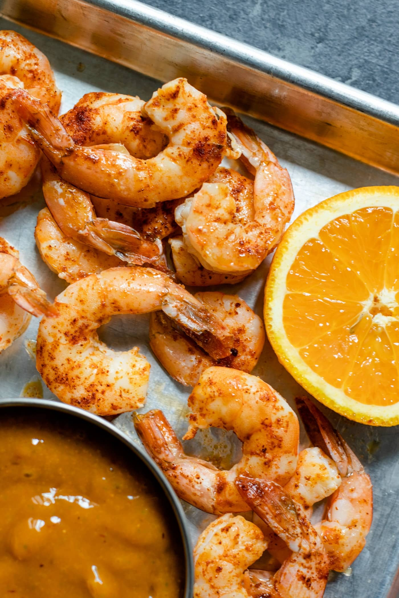Pieces of chipotle shrimp on roasting sheet with slice of orange and bowl of mango sauce on a gray concrete surface