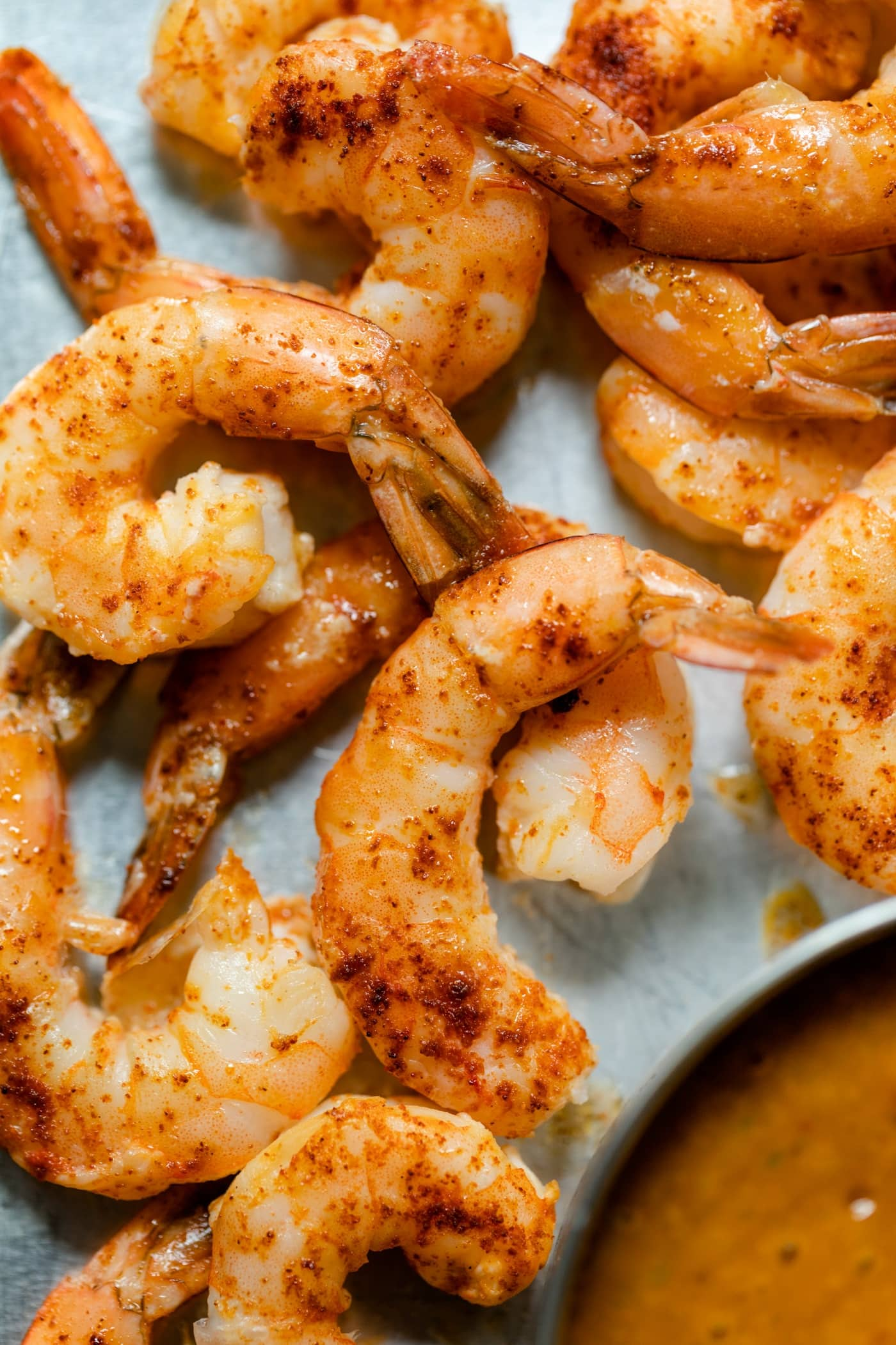 Top down view of pieces of chipotle shrimp with tails attached on roasting sheet with bowl of mango sauce on a gray concrete surface