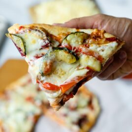 Piece of homemade roasted vegetable pizza being held with rest of pizza in background on top of white parchment with pizza board and extra cheese on butting board all on marble surface