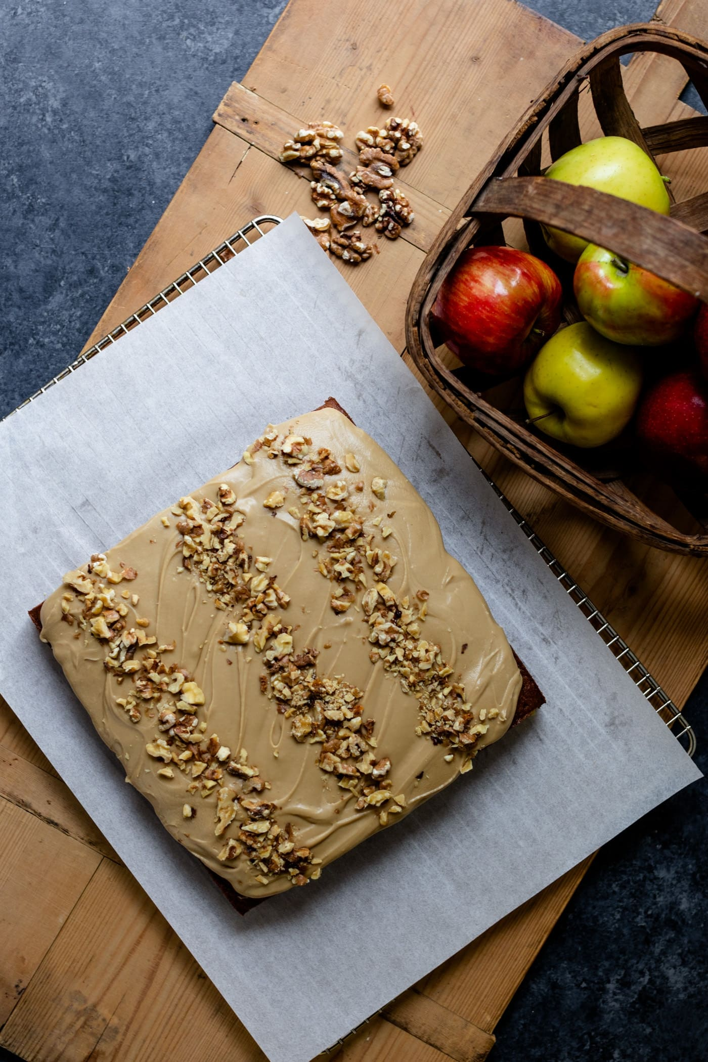 Top down view of applesauce cake with caramel frosting on a piece of parchment sitting on wood board with basket of red and yellow apples and chopped walnuts on a gray slate surface