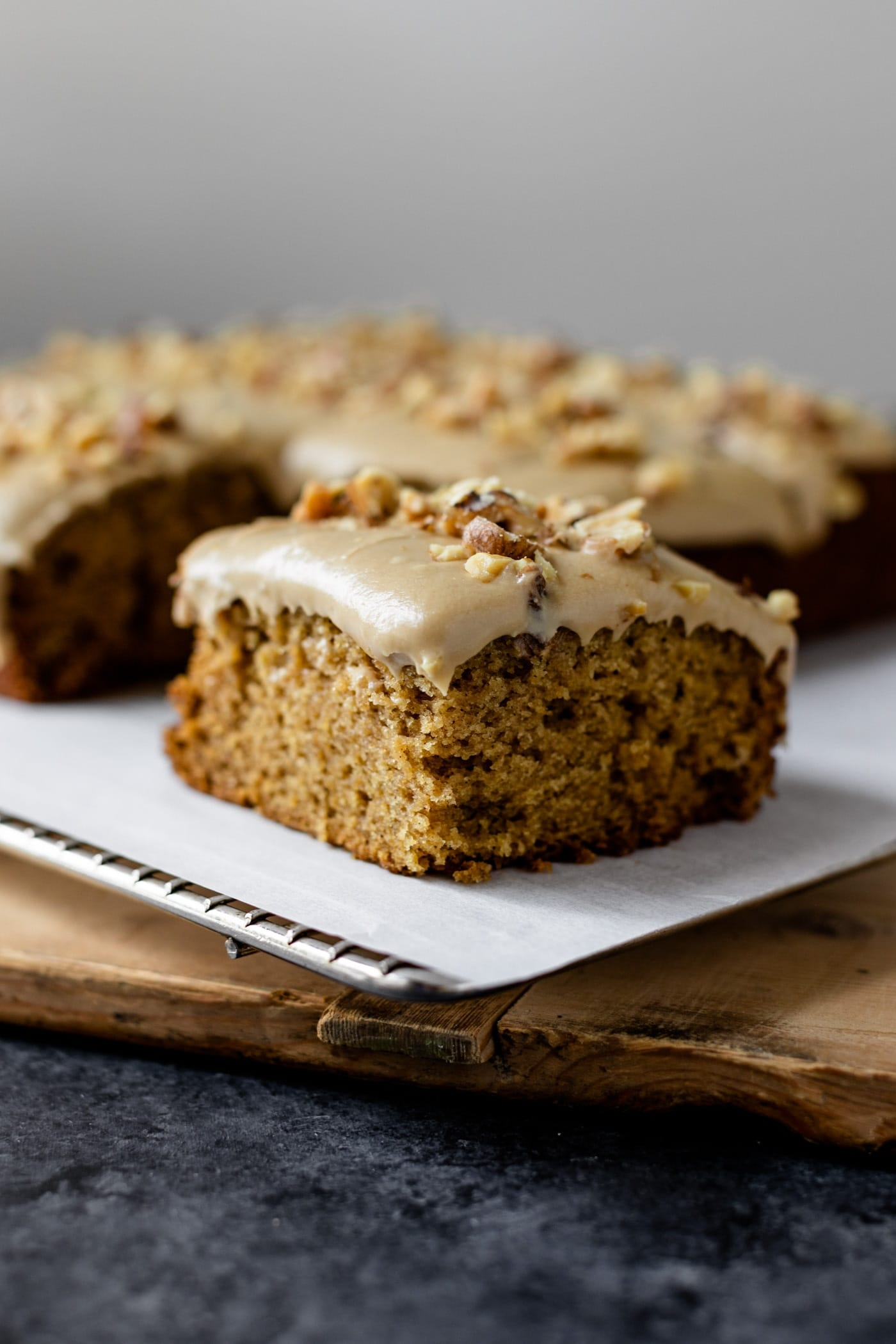 Piece of applesauce cake with caramel frosting topped with toasted walnuts sitting on piece of parchment with rest of cake behind all on wood board on gray slate surface