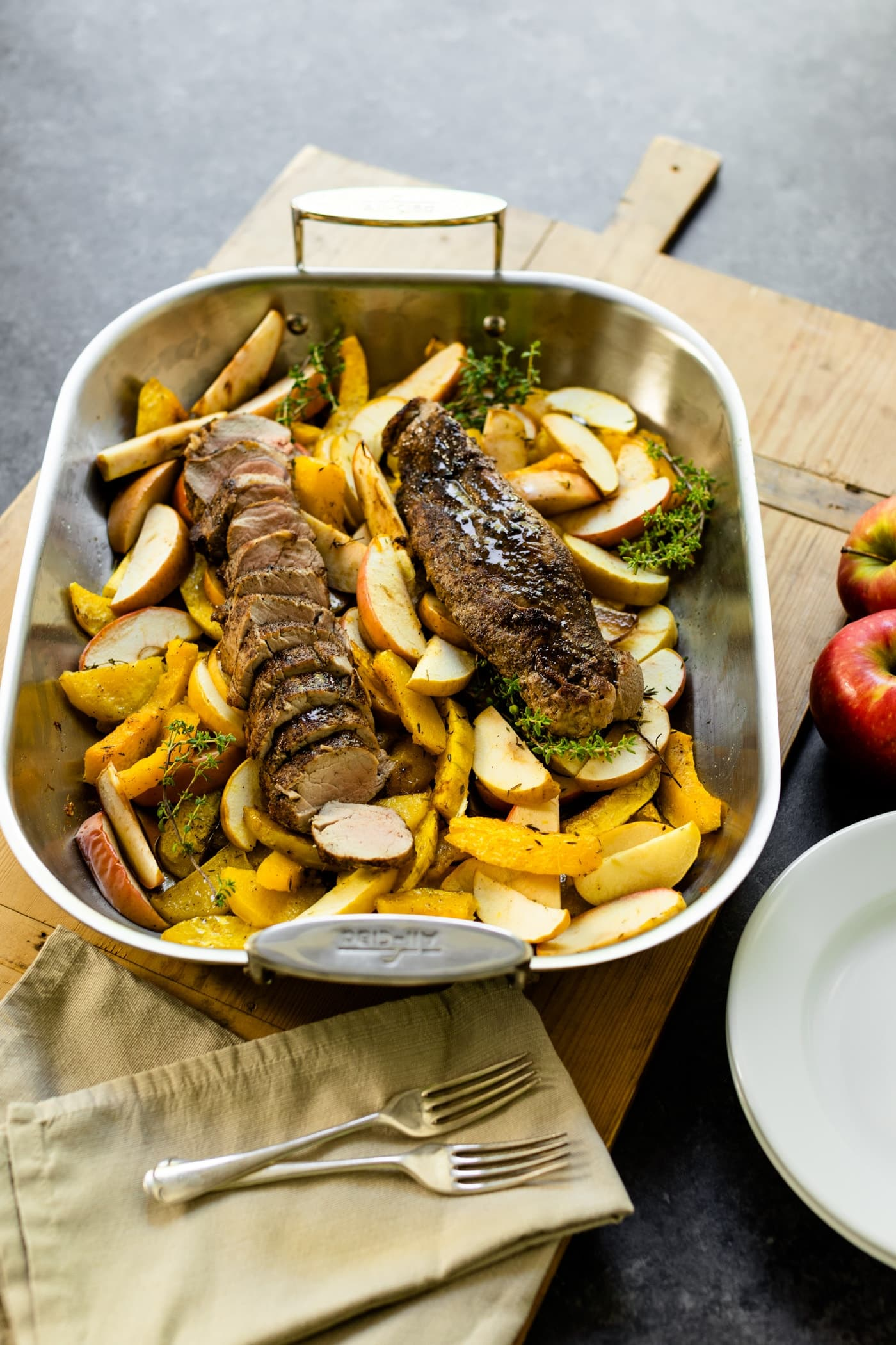 Pan full of roasted pork tenderloin sitting on bed of roasted apples and squash with wood board, plates, napkin and extra apples all on a gray slate surface