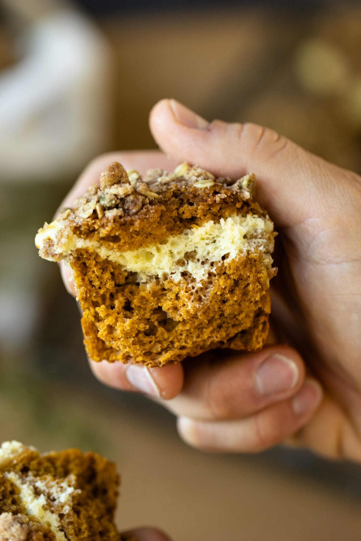 Pumpkin cheesecake muffins torn in half with cheesecake middle exposed held by hand with extra muffins and cooling rack in background