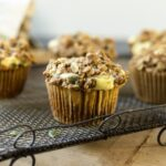 Pumpkin cheesecake muffins sitting on decorative wire cooling rack on wood board with basket full of muffins and towel in background all on gray slate surface with with background