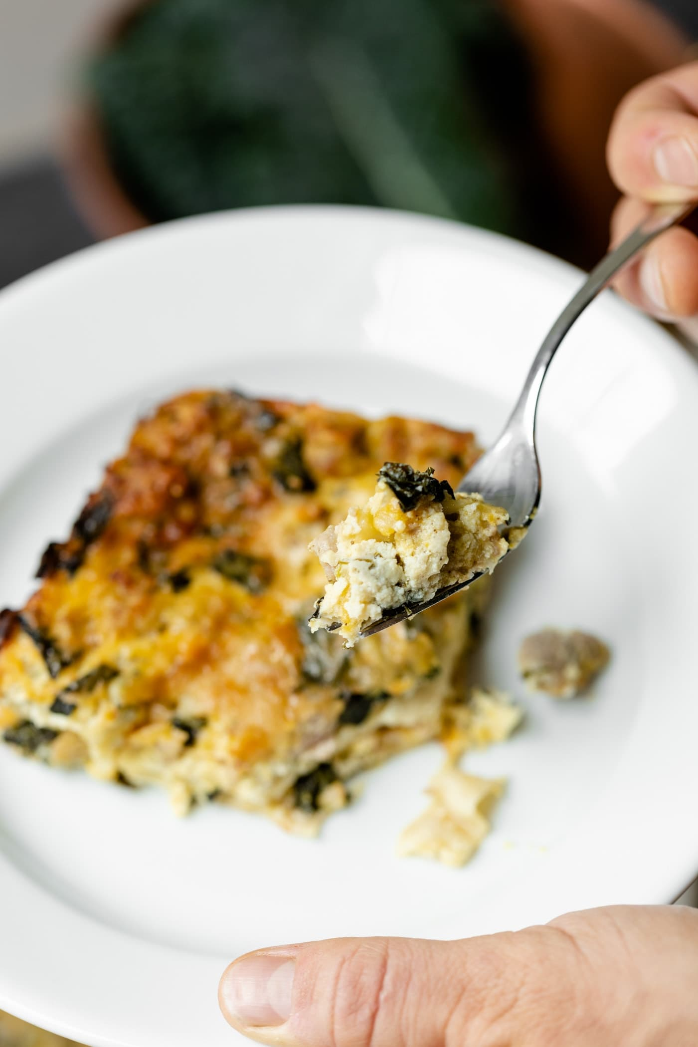 Piece of squash kale lasagna held by hand on a white plate with fork holding piece of dish with copper pot and kale in background on gray slate surface