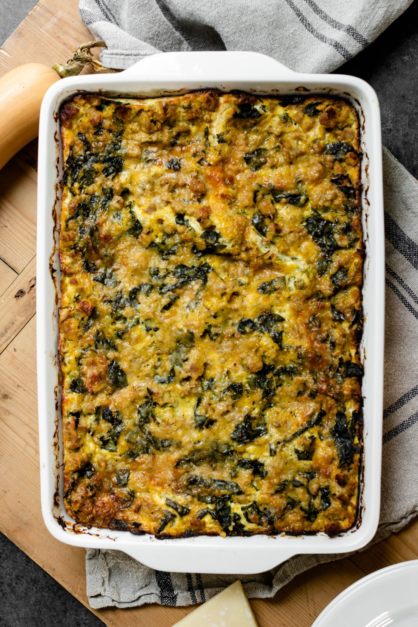 Top down view of squash kale lasagna in white baking dish sitting on wood board with Parmesan cheese, squash and towel underneath all on gray slate surface