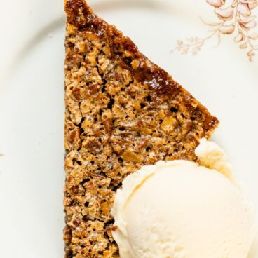 Pecan pie bars sitting on white plate with scoop of vanilla ice cream on top with linen napkin to the side