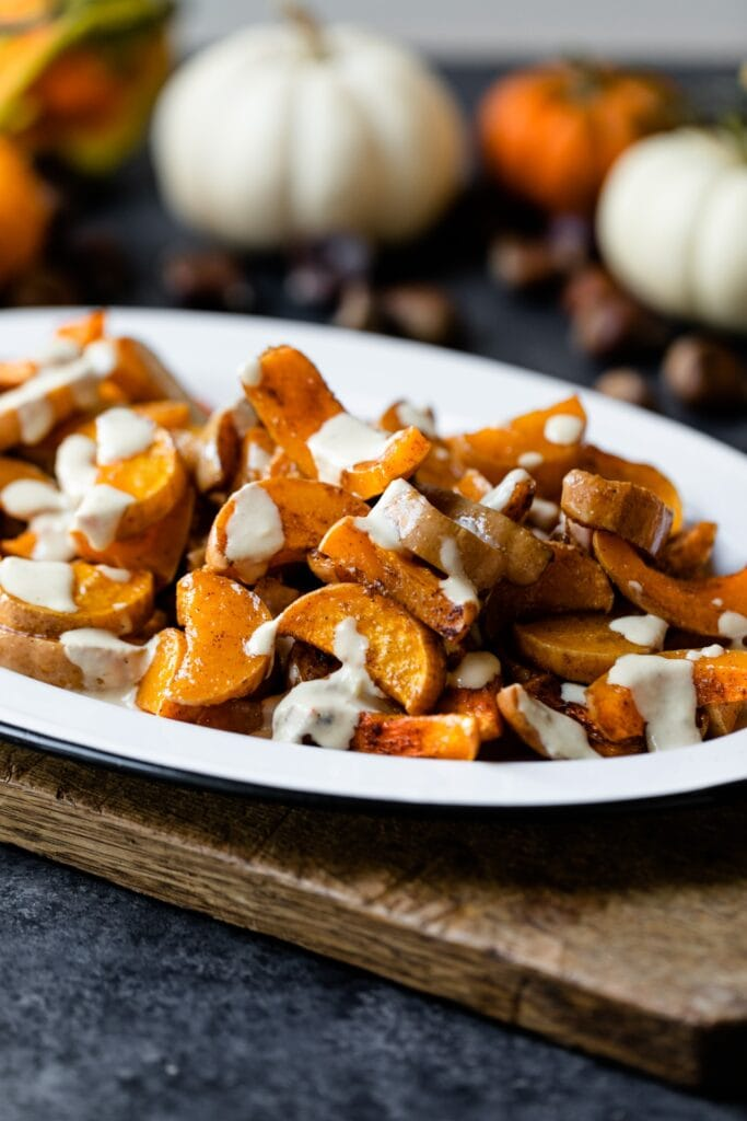 Spiced butternut squash on a white platter sitting on wood board with pumpkins and nuts in background on a gray slate surface