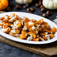Spiced butternut squash sprinkled with tahini sauce in a white platter sitting on wood board with pumpkins and nuts in background on gray slate surface