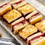 Turkey cranberry croque monsieur sandwiches sitting on white plate with linen napkin underneath on white surface