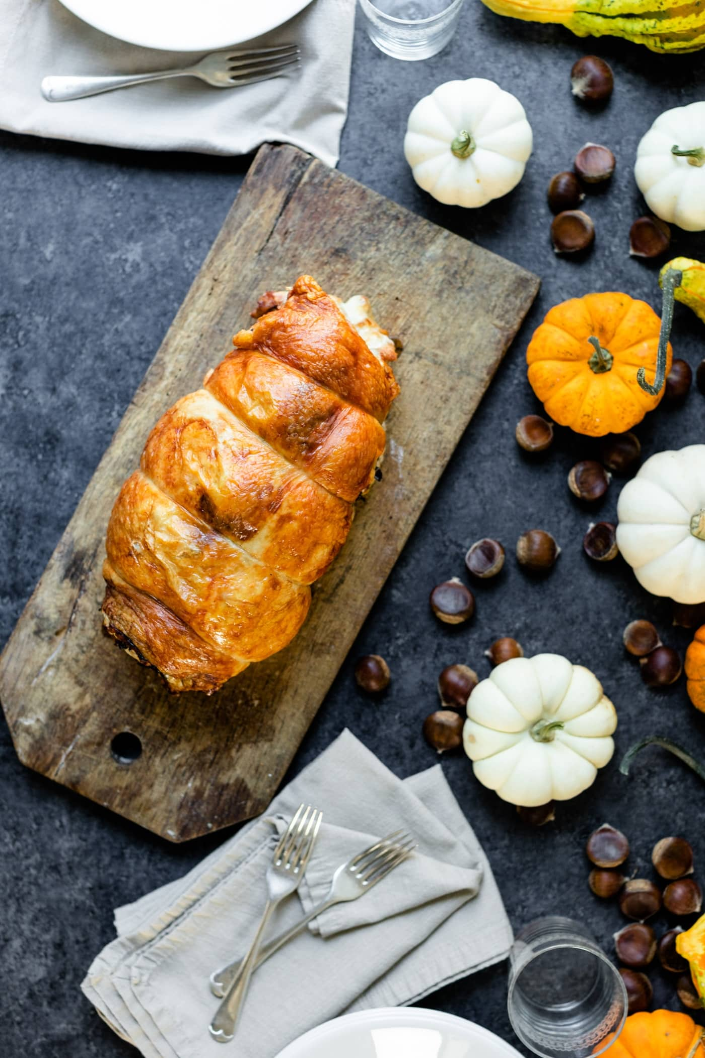 Turkey roulade sitting on wood board with white and orange pumpkins, linen napkins and plates on a gray slate surface