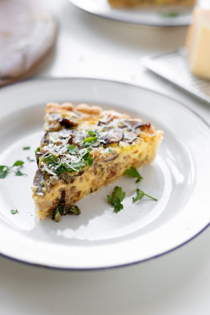 Breakfast quiche topped with parsley and Parmesan cheese sitting on white plate with extra cheese and bread board in background all on white surface
