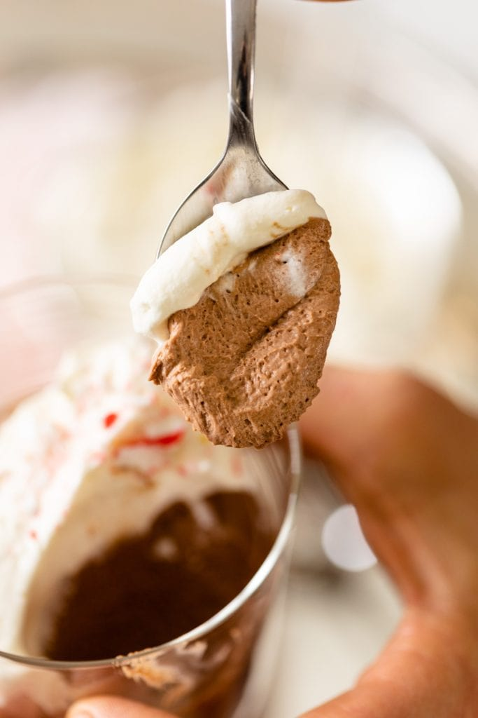 Chocolate mousse sitting on spoon held by hand with extra glasses of chocolate mousse topped with whipped cream and peppermint bits in background
