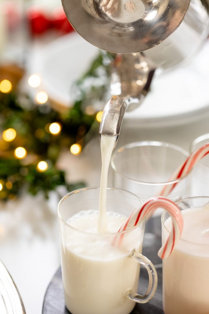 Stainless steel kettle pouring white hot chocolate into glasses with candy cane sitting on edge all on white surface with Christmas lights in background