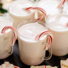 White hot chocolate in glasses with candy cane inside with extra pieces of peppermint bark all on white surface
