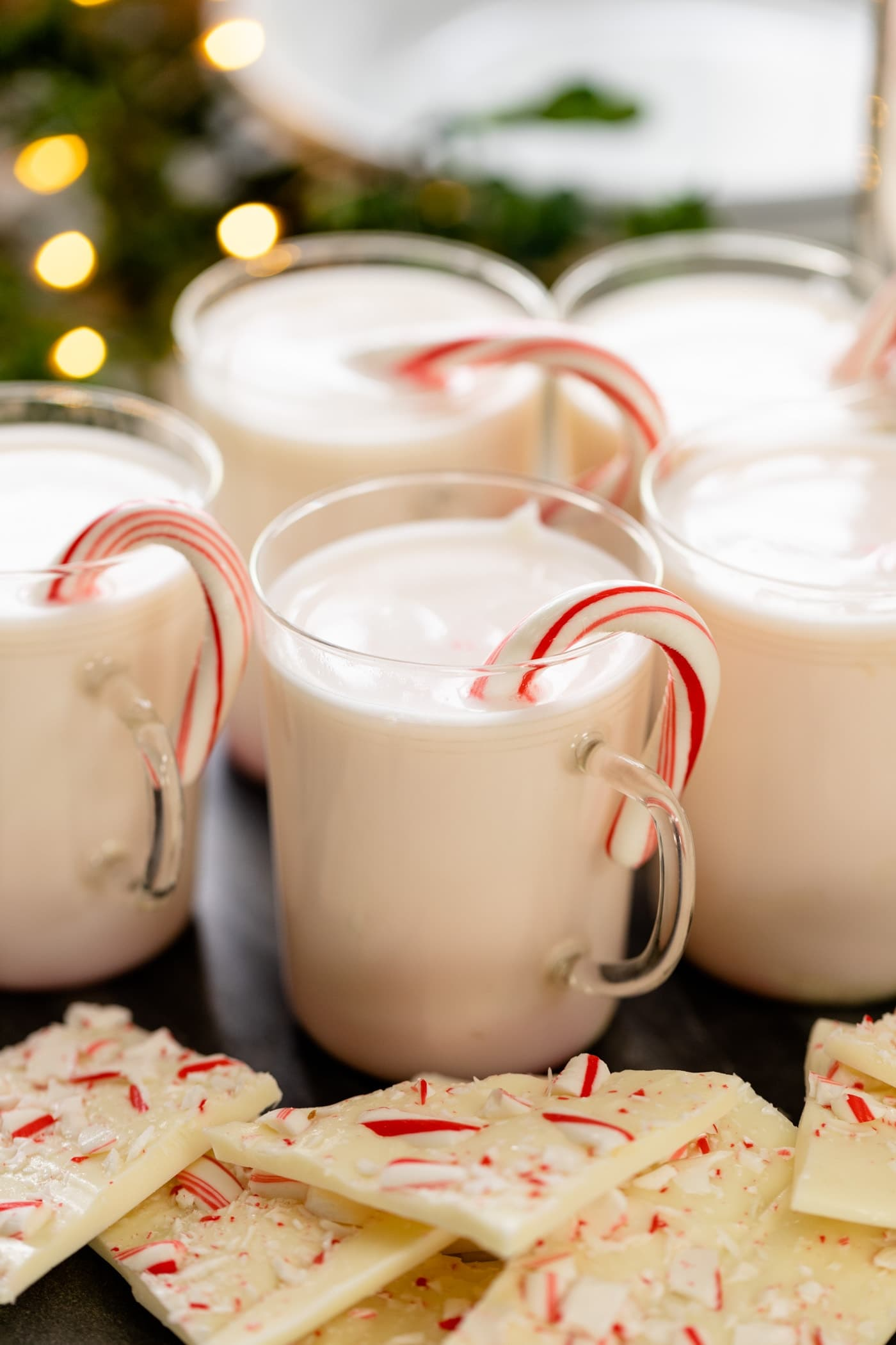Peppermint flavored white hot chocolate in glass mug with candy cane sitting on edge with extra peppermint bark in front all on white surface with Christmas lights in background