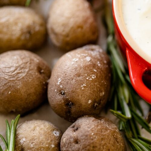 Salt roasted potatoes sitting in a bed of salt with rosemary sprigs place around with red bowl filled with rosemary Ranch dipping sauce