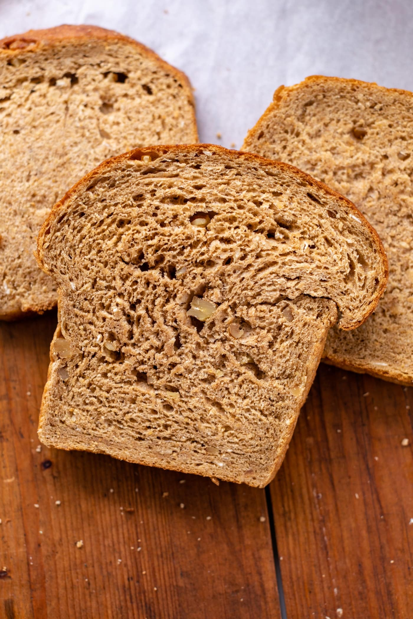 Hearty grain bread sitting on wood board with white piece of parchment in background along with other slices of bread