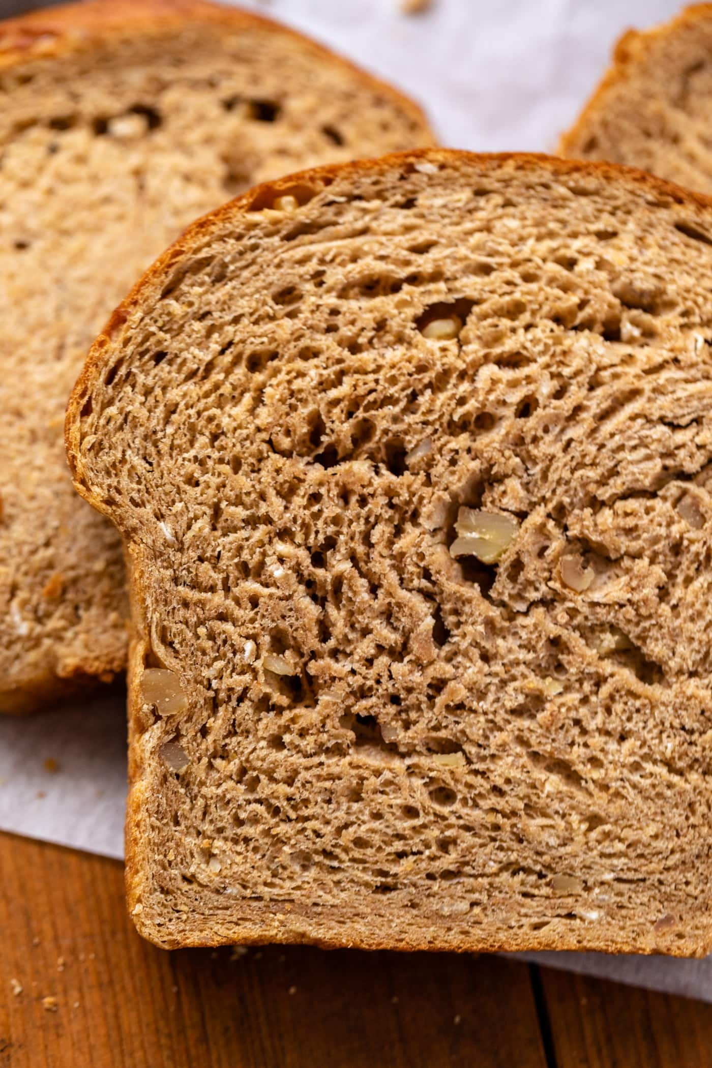 Close up view of inside of one piece of hearty grain bread with extra slices of bread in background on wood surface with parchment underneat