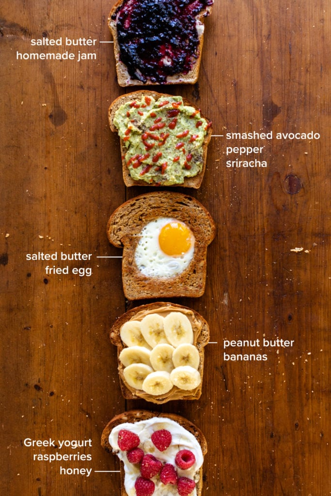 Five versions of hearty grain bread sitting on piece of wood, each topped with a unique combination including jam, avocado, an egg, banana and peanut butter and yogurt with raspberries