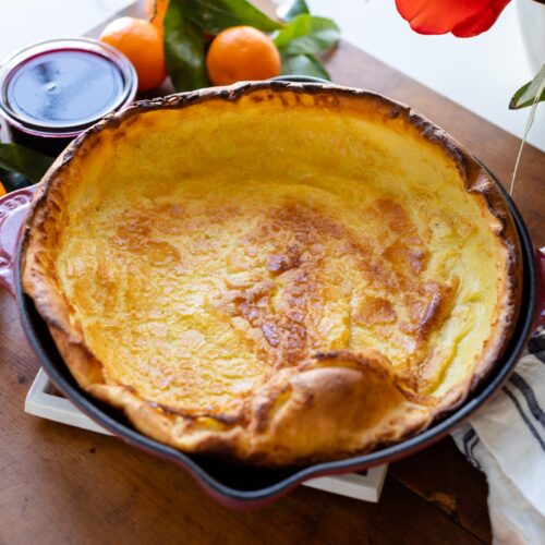 Citrus Dutch baby sitting in a red skillet surrounded by oranges and coulis sauce all on wood board on white surface