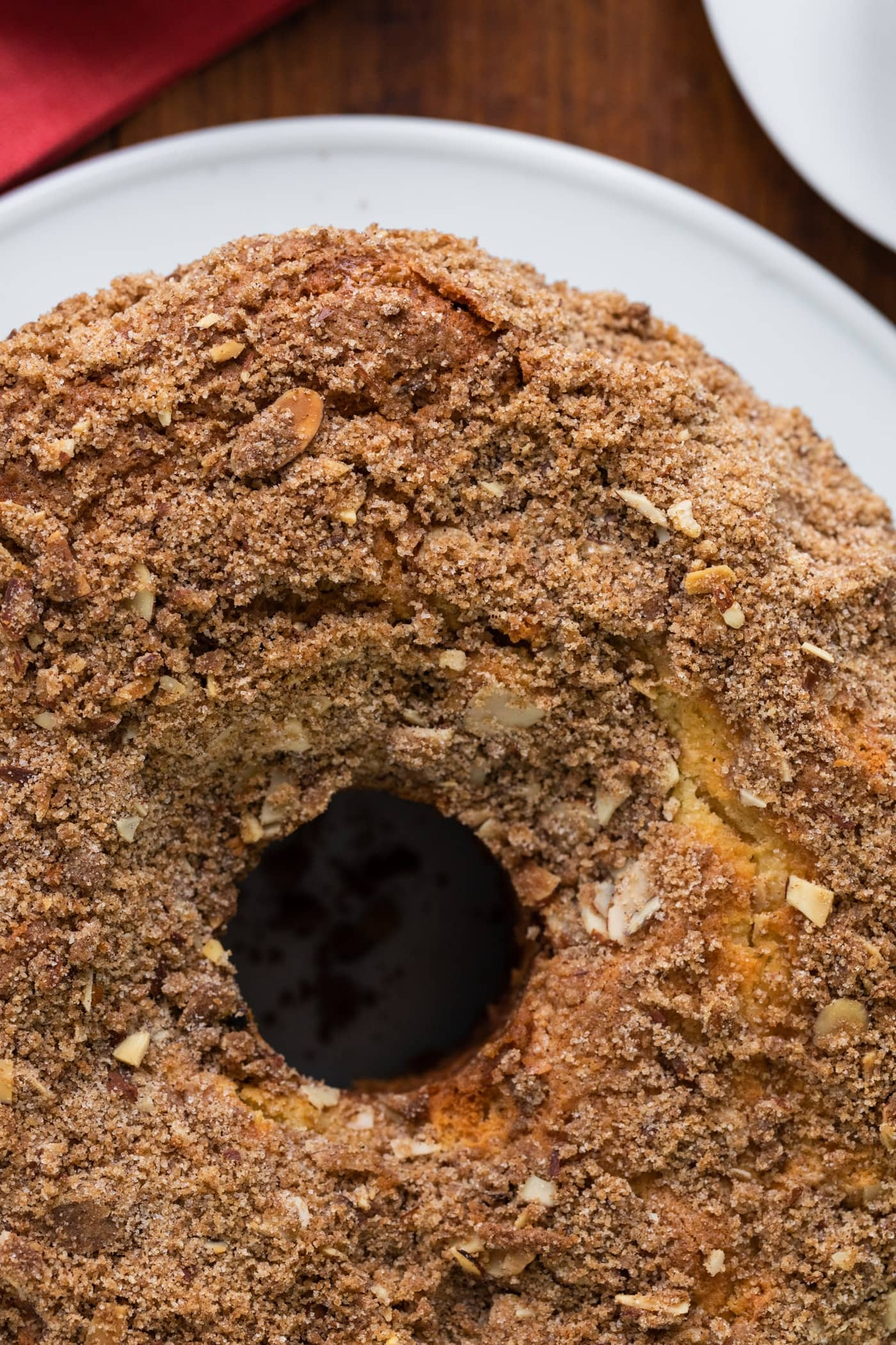 Top down view of streusel topping on top of a coffee cake with hole down the center with red napkin in background