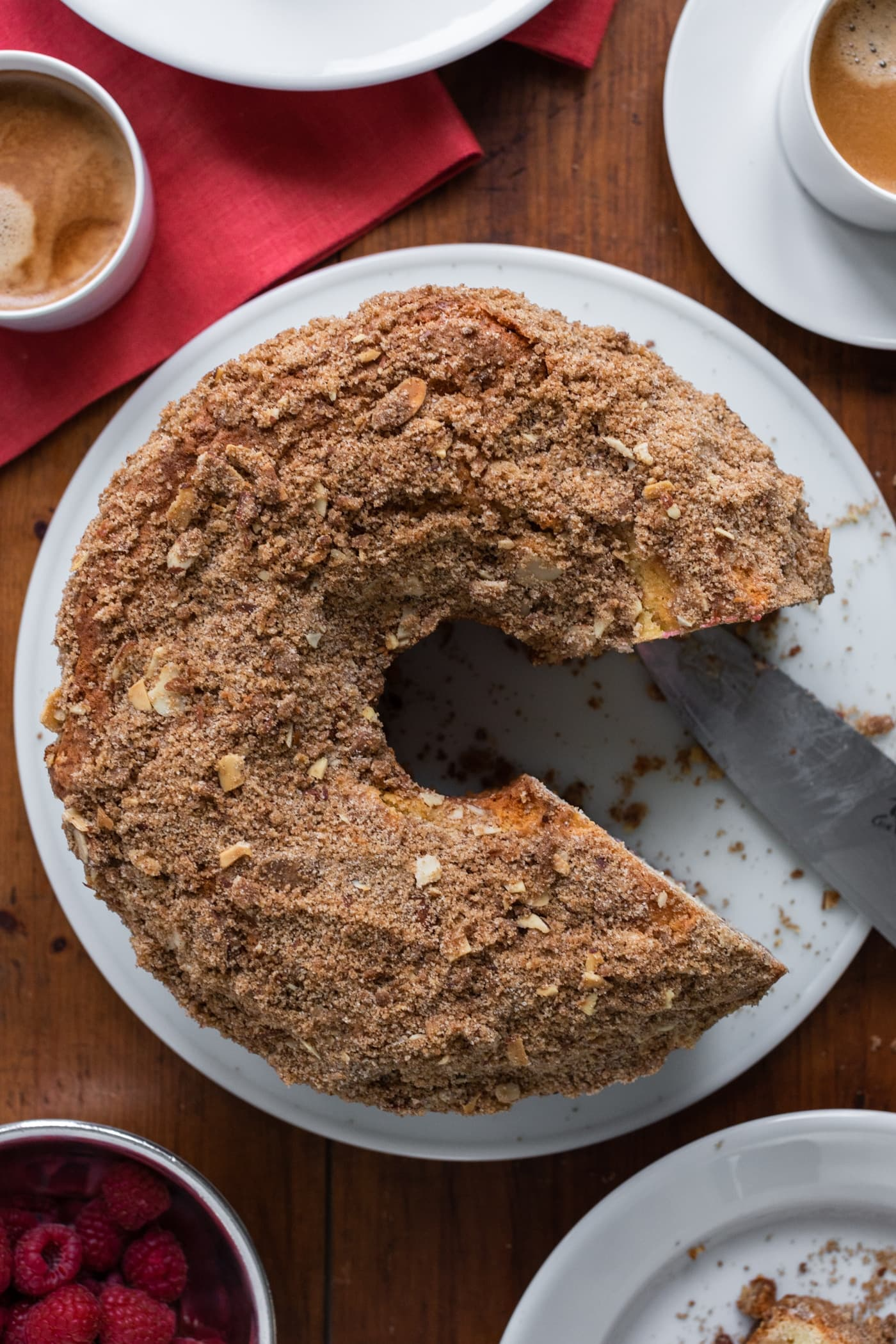 Top down view of coffee cake sitting on red clothes with knife sitting on plate after cutting slices