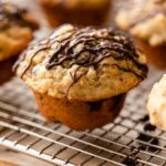 Banana chocolate chunk muffins sitting on wire cooling rack on wood board with piece of parchment underneath