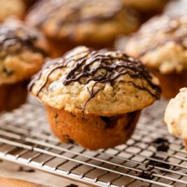 Banana chocolate chunk muffin sitting on wire cooling rack on wood board surrounded by other muffins all drizzled with chocolate on top