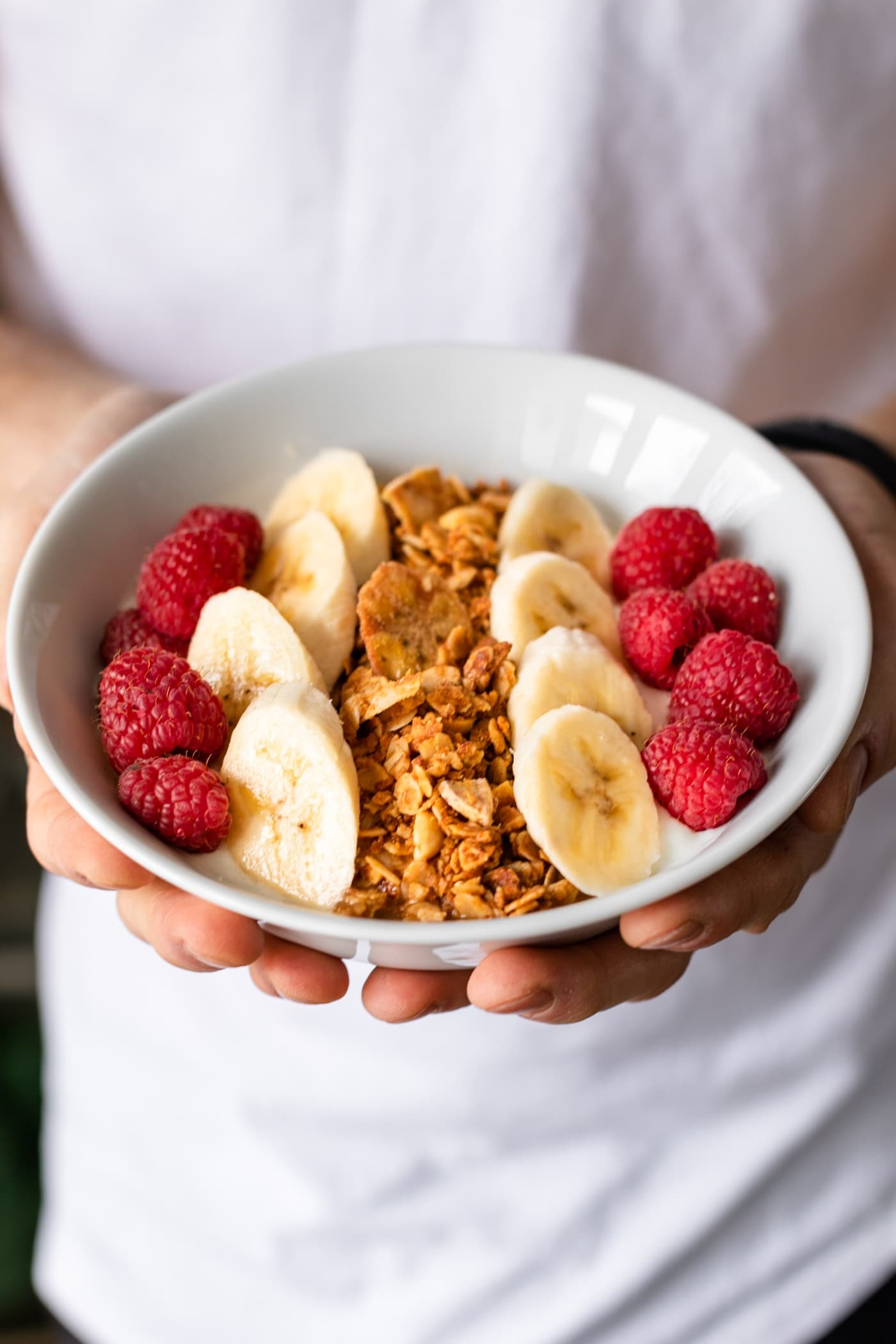 Hands holding bowl of peanut butter granola with white shirt and black pants in background