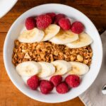 Top down video of homemade peanut butter granola sitting on top of yogurt in a white bowl along with bananas and raspberries with spoons and napkin all on wood surface