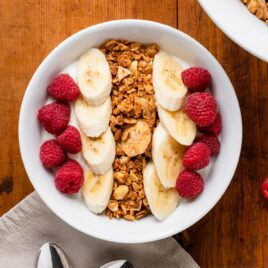 Top down view of granola in bowl on top of yogurt nestled among raspberries and bananas all on wood surface