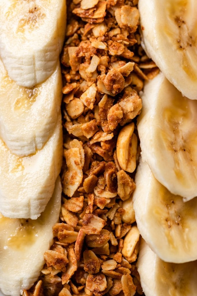 Close up view of homemade peanut butter granola nestled in between slices of banana