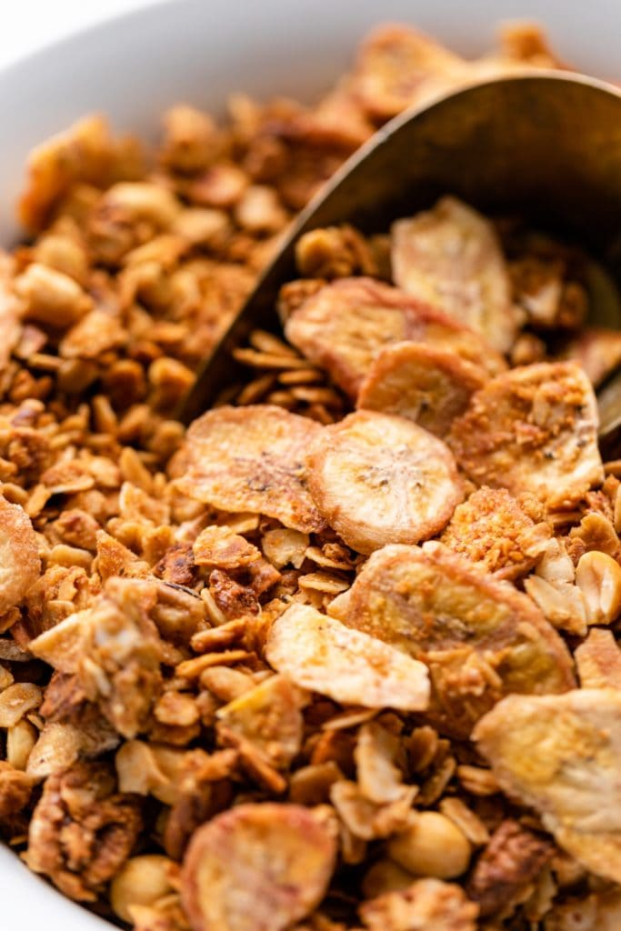 Granola with pieces of dried banana chips sitting in white bowl with gold scoop in background
