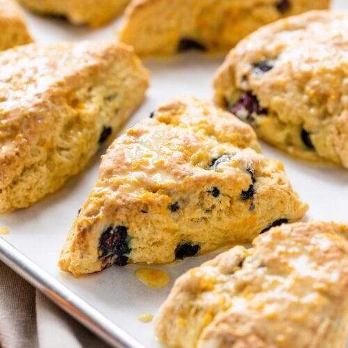 Orange and blueberry Irish soda bread scones topped with glaze sitting on parchment-lined baking sheet