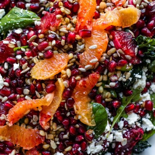 Top down view of blood orange and wheat berry salad sitting on white platter sprinkled with pomegranate arils and feta cheese