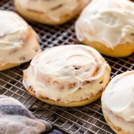 Ultimate cinnamon roll sitting on wire cooling rack surrounded by other cinnamon rolls frosted with cream cheese frosting