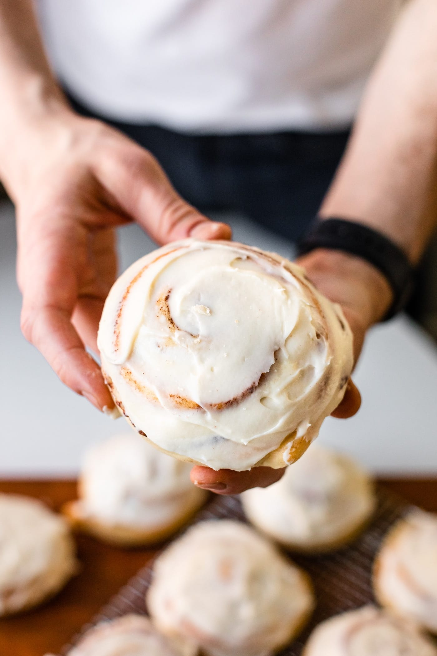 Two hands holding cinnamon roll frosted with cream cheese frosting with extra cinnamon rolls cooling in background