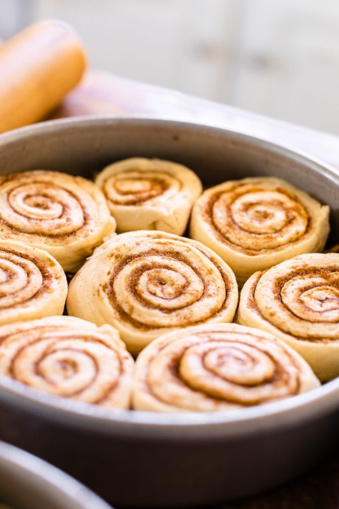 Unbaked cinnamon rolls sitting in metal pan ready to rise and swirled with cinnamon and sugar mixture