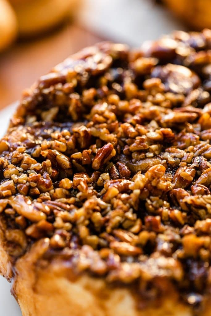 Sticky caramel roll recipe topped with chopped pecans and drizzled with a caramel sauce