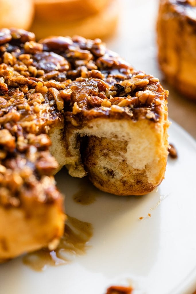 Inside view of sticky caramel rolls with one piece missing topped with chopped pecans and caramel sauce