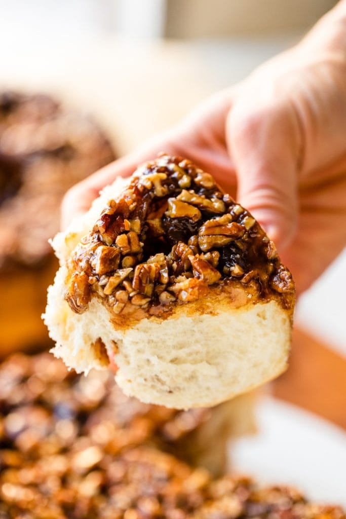 Hand holding cinnamon roll topped with sticky caramel sauce with chopped pecans and caramel sauce on top with extra rolls in background