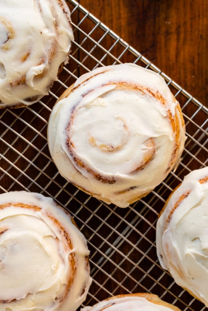 Top down view of ultimate cinnamon roll recipe sitting on wire cooling rack surrounded by other cinnamon rolls all frosted with white cream cheese frosting all on wood surface