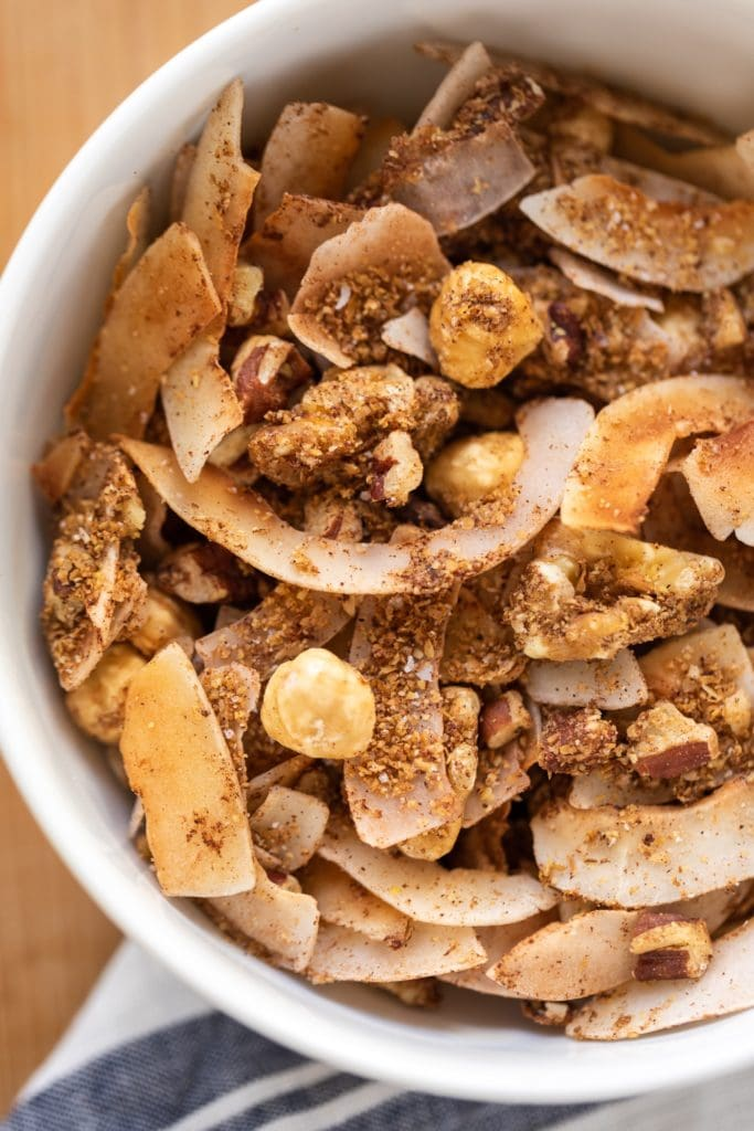 Coconut and nut granola sitting in white bowl with white and blue linen napkin all on wood surface