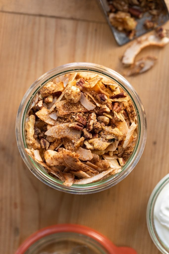 Top down view of grain-free granola in glass container sitting on wood surface with extra granola sitting on side