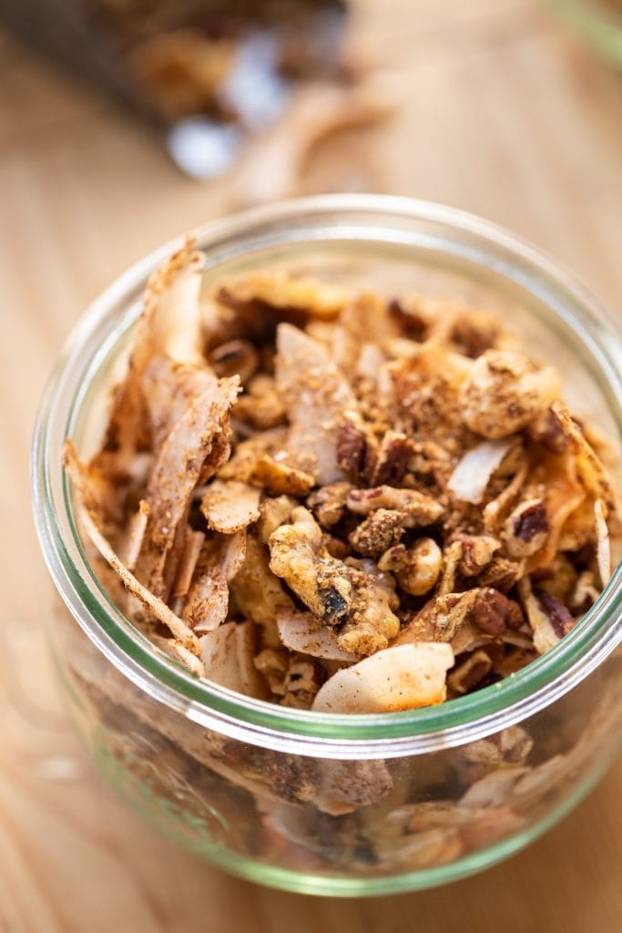 Glass container filled with granola made of coconut and nuts on wood surface