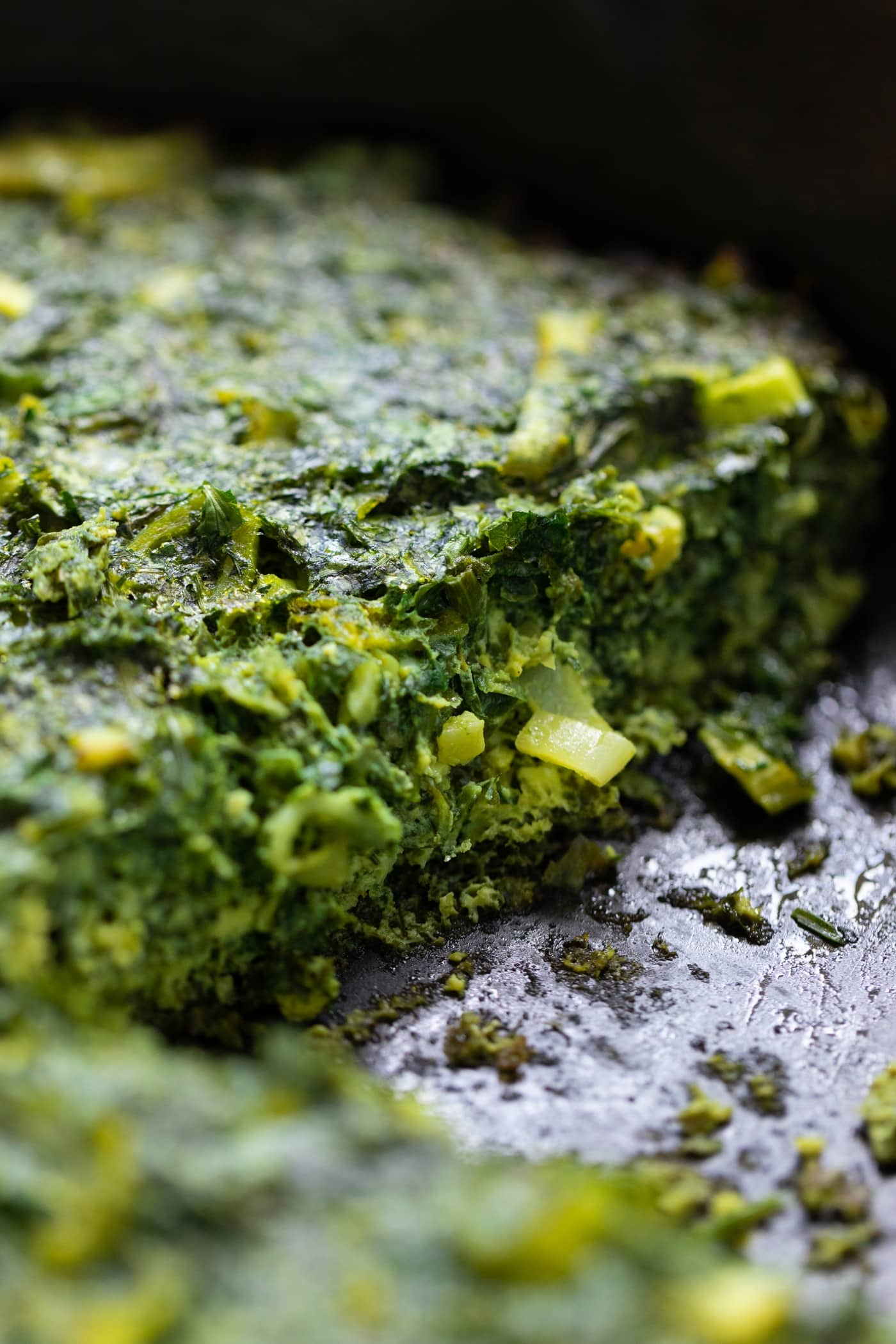 Close up view of inside of herb omelet with leek protruding all in cash iron pan