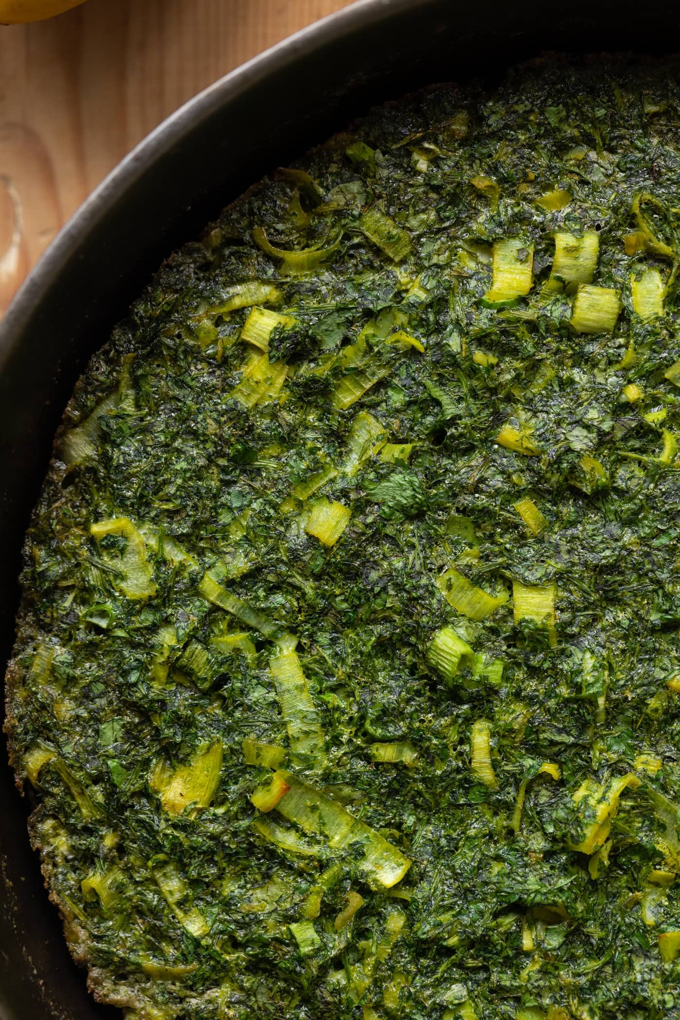 Top down view of herb omelet dotted with leeks and herbs in cast iron skillet on wood surface