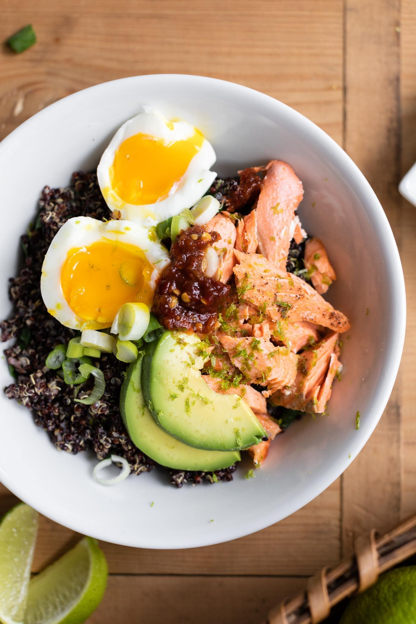 Top down view of salmon bowl topped with sliced egg and avocado all on wood surface