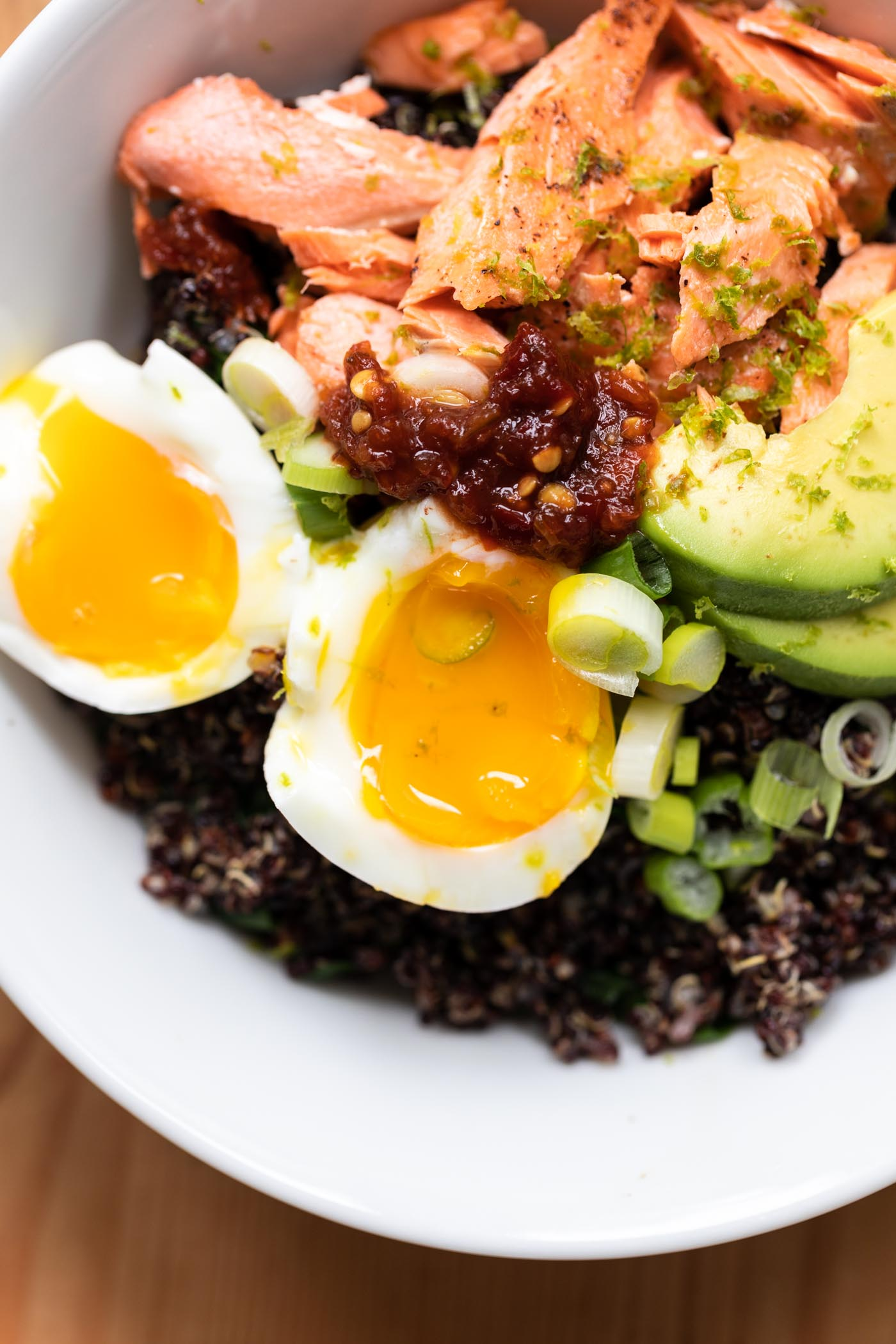Salmon bowl filled with quinoa, avocado, and sliced open egg all on wood surface
